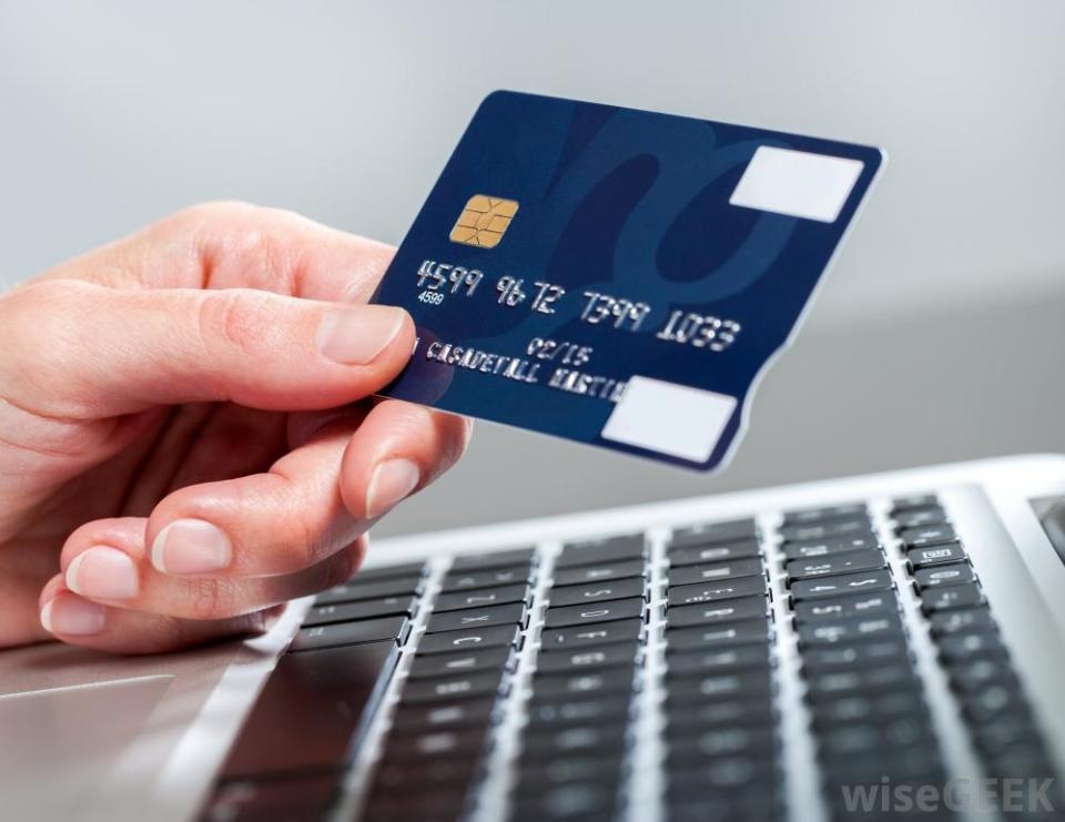 person-holding-credit-card-over-keyboard.jpg